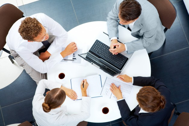 business people sat around a round table having a meeting